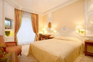 A bed or beds in a room at Colombi Hotel