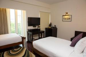 A bed or beds in a room at The Midori by Lakeshore, Gulshan , Dhaka