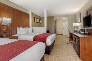 A bed or beds in a room at Comfort Suites Speedway - Kansas City