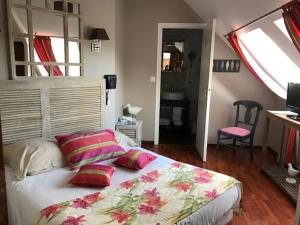 A bed or beds in a room at Hotel Logis Beauséjour