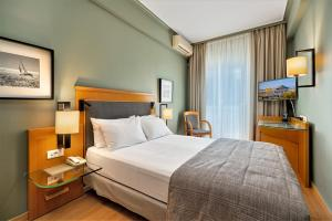 A bed or beds in a room at Plaka Hotel