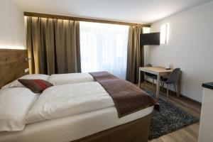 A bed or beds in a room at B-Inn Apartments Zermatt