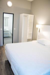 A bed or beds in a room at Hôtel Calm Lille