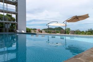 The swimming pool at or near El Faro Beach Hotel