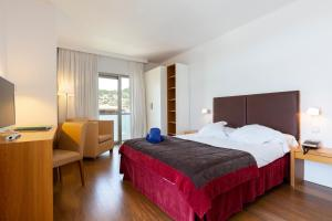 A bed or beds in a room at Aimia Hotel