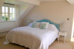 A bed or beds in a room at Thatched Cottage