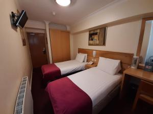 Säng eller sängar i ett rum på Americana Hotel