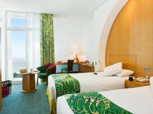 سرير أو أسرّة في غرفة في مركيور جراند جبل حفيت