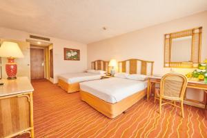 A bed or beds in a room at The Galadari Hotel