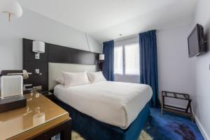 A bed or beds in a room at Hôtel 15 Montparnasse
