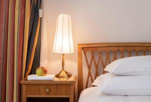 A bed or beds in a room at Parkhotel Laurin