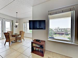 A television and/or entertainment center at New Listing! Modern Beach Condo With Infinity Pool Condo