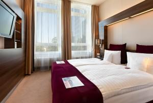 A bed or beds in a room at Flemings Selection Hotel Frankfurt-City