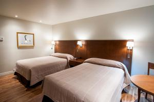 A bed or beds in a room at Motel Mistral
