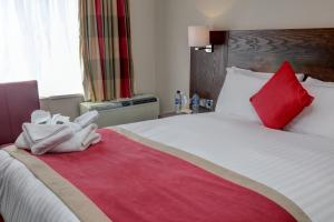 A bed or beds in a room at Best Western The Stuart Hotel