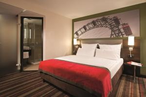 A bed or beds in a room at Leonardo Hotel Vienna