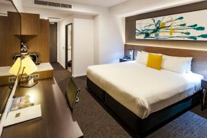 A bed or beds in a room at Mercure Sunshine Coast Kawana Waters