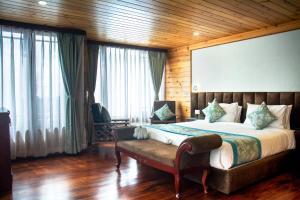 A bed or beds in a room at Udaan Dekeling Resort, Darjeeling