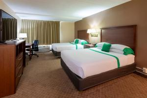 A bed or beds in a room at GuestHouse Inn & Suites Rochester