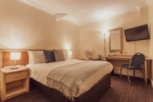 A bed or beds in a room at The Gardens Hotel