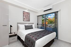 A bed or beds in a room at Argus Hotel Darwin