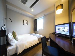 A bed or beds in a room at Meitetsu Inn Nagoya Sakuradori