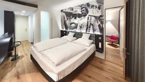 A bed or beds in a room at V8 HOTEL Motorworld Region Stuttgart