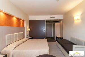 A bed or beds in a room at Grand Hotel Olimpo