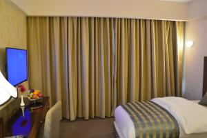A bed or beds in a room at Saray Hotel Amman