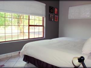 A bed or beds in a room at Aqua Terra Guest House