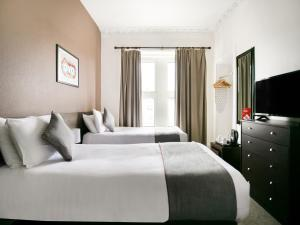 A bed or beds in a room at OYO Corner Hotel