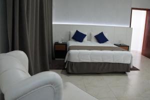 A bed or beds in a room at Fenix Hotel Pouso Alegre