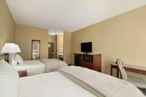 A bed or beds in a room at Days Inn & Suites by Wyndham Brandon