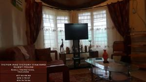 A television and/or entertainment center at VICTOR AND VICTORY GUESTHOUSE Annexe