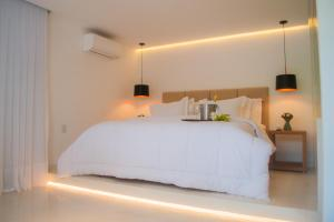 A bed or beds in a room at Pipa Lagoa Hotel