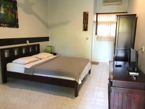 A bed or beds in a room at Mangga Bali Inn