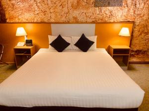 A bed or beds in a room at Desert Cave Hotel