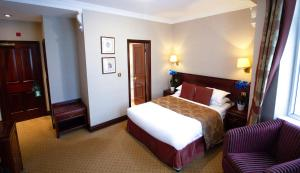 A bed or beds in a room at Rochester Hotel by Blue Orchid