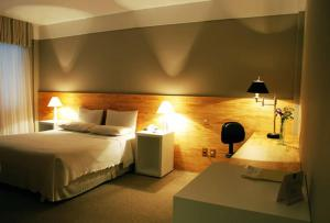 A bed or beds in a room at Planalto Hotel