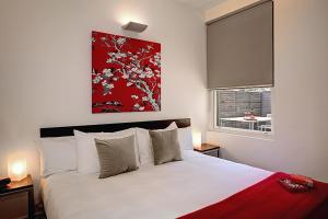 A bed or beds in a room at Plum Serviced Apartments North Melbourne