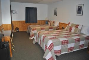 A bed or beds in a room at Aspen Inn