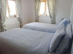 A bed or beds in a room at Brook Lodge Country Cottage
