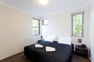A bed or beds in a room at Bluegum Apartments Newcastle