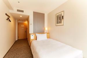 A bed or beds in a room at Hotel Agora Osaka Moriguchi