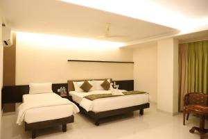 A bed or beds in a room at Kyriad Hotel Vijayapura by OTHPL