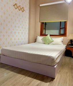 A bed or beds in a room at The Queen Hotel & Spa