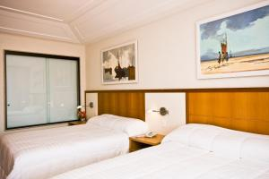 A bed or beds in a room at Hotel Ferradura Resort