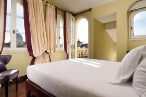 A bed or beds in a room at Hotel L'Orologio