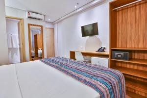 A bed or beds in a room at Maringá Airport Hotel