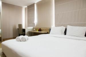 A bed or beds in a room at Homey 1BR at Enviro Apartment Cikarang By Travelio